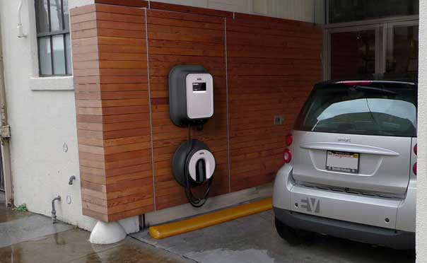 Smart car parked in a garage near an electric vehicle charger