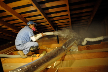 An energy doctor applying blown-in insulation to an attic space.