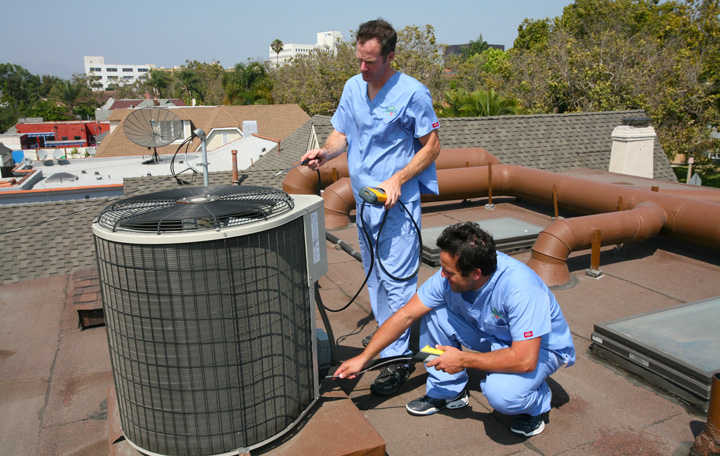 Two Energy Doctors performing maintenance on a rooftop HVAC unit