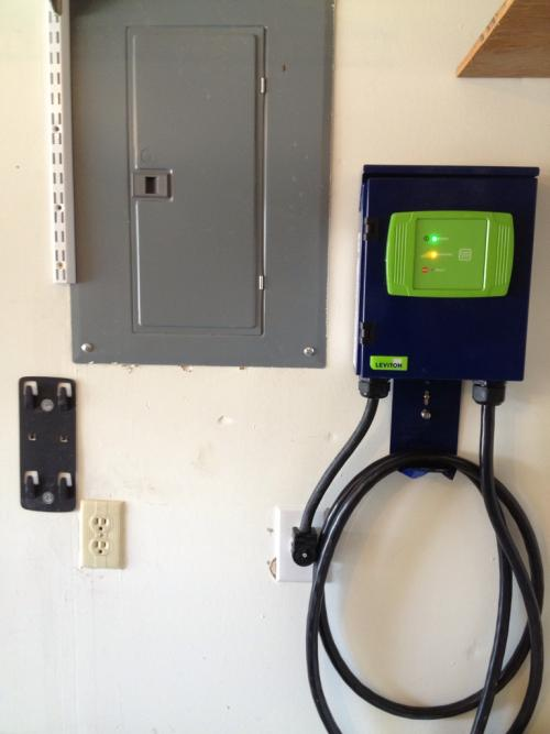 electric vehicle charger plugged in near a breaker box
