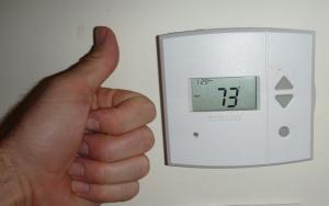 Person giving a thumbs up to their thermostat - set precisely at 73 degrees.